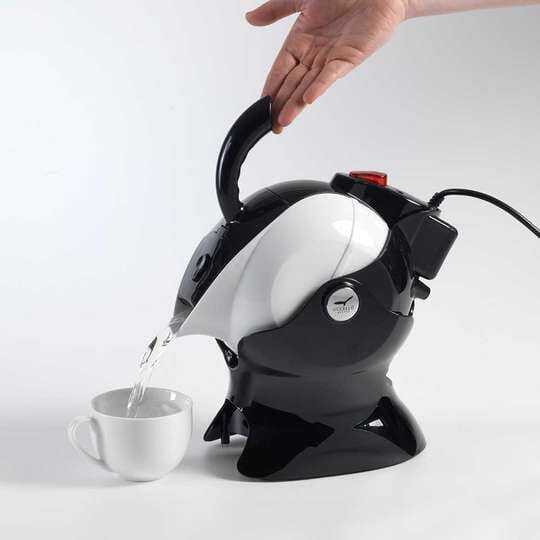 A hand gently tipping the easy pour kettle in its tipper to fill a cup with hot water