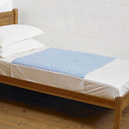 A blue Kylie Bed Pad on a bed