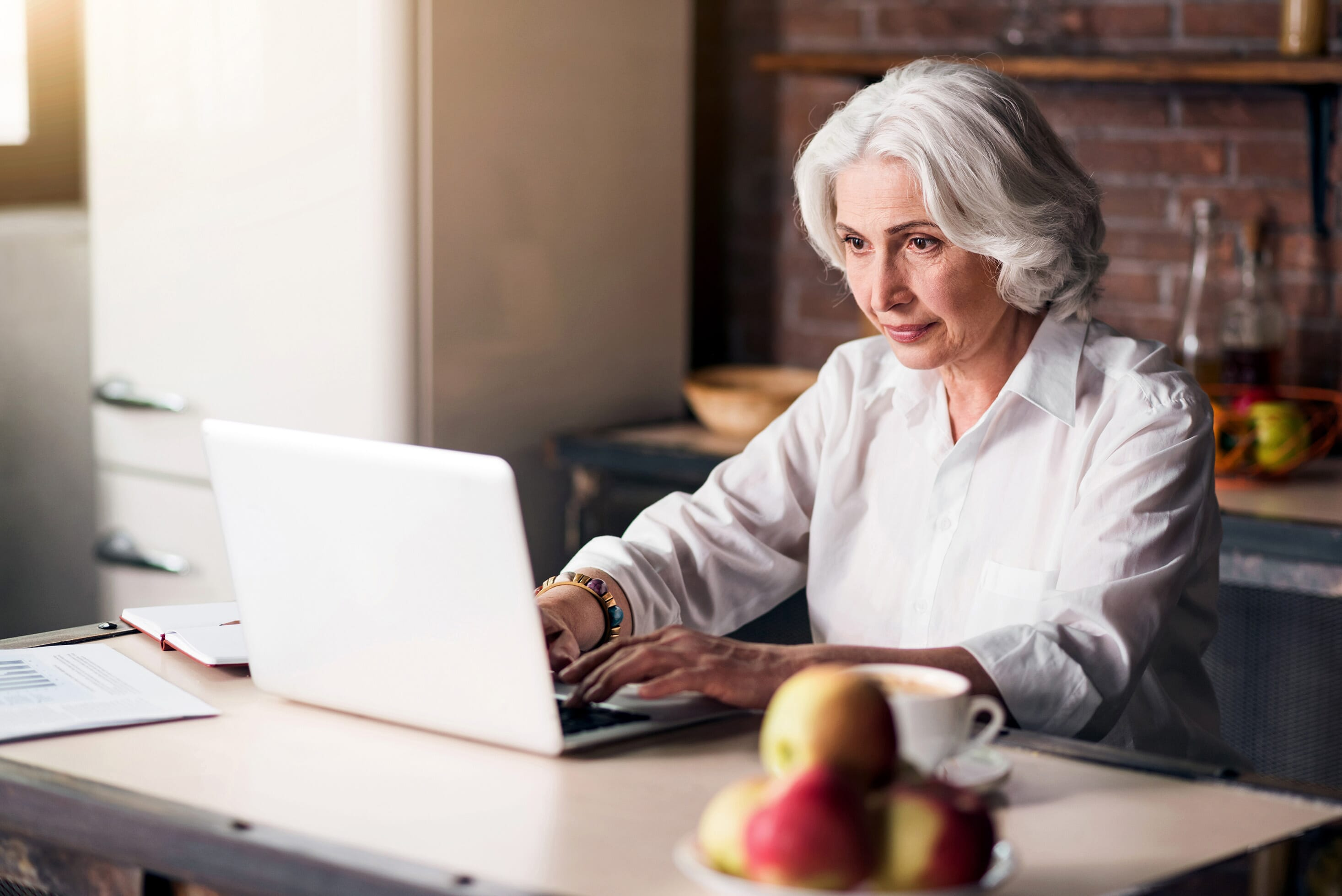 older woman using her laptop to write an email