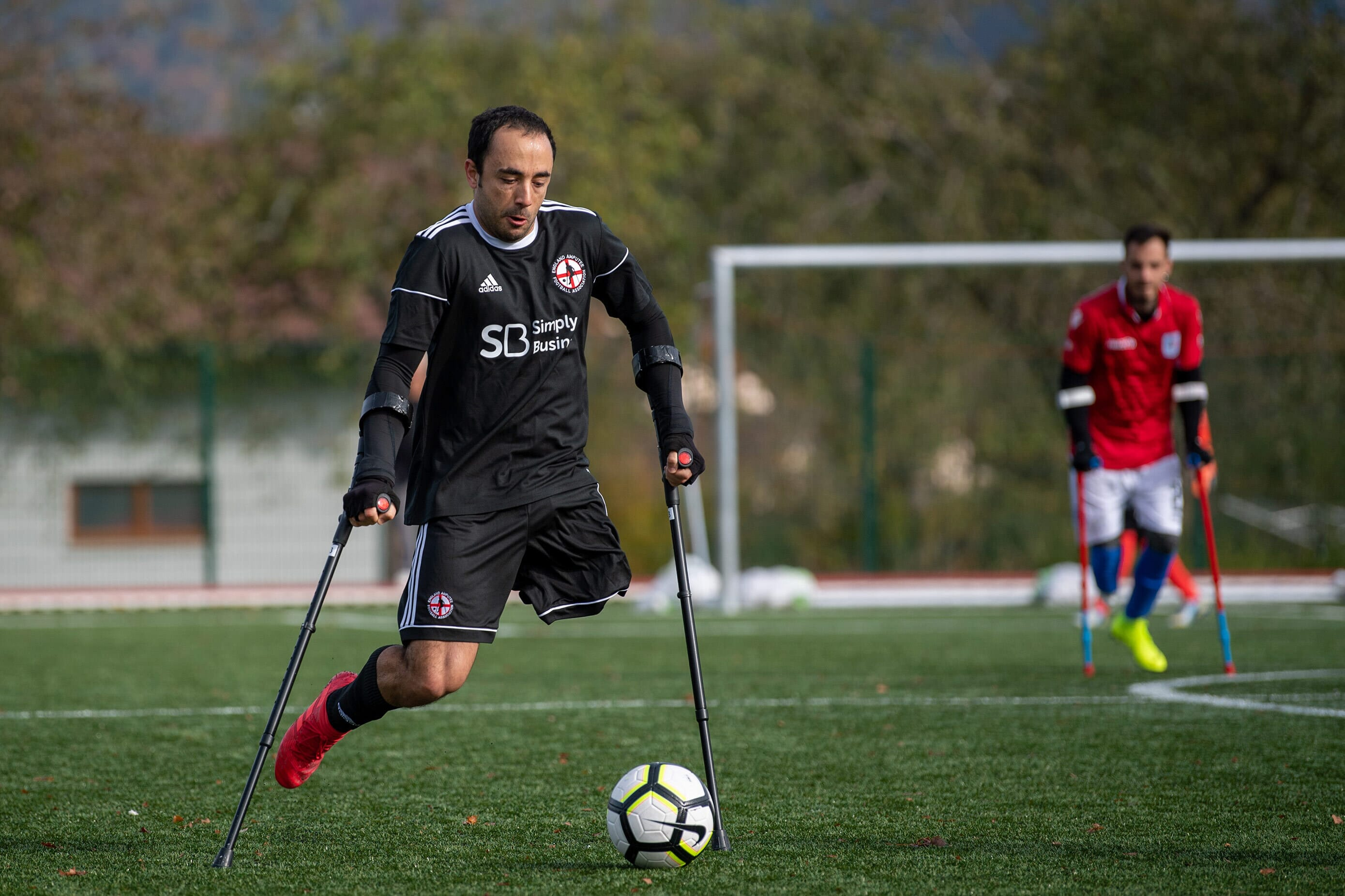 man on crutches with one leg moving to kick the football