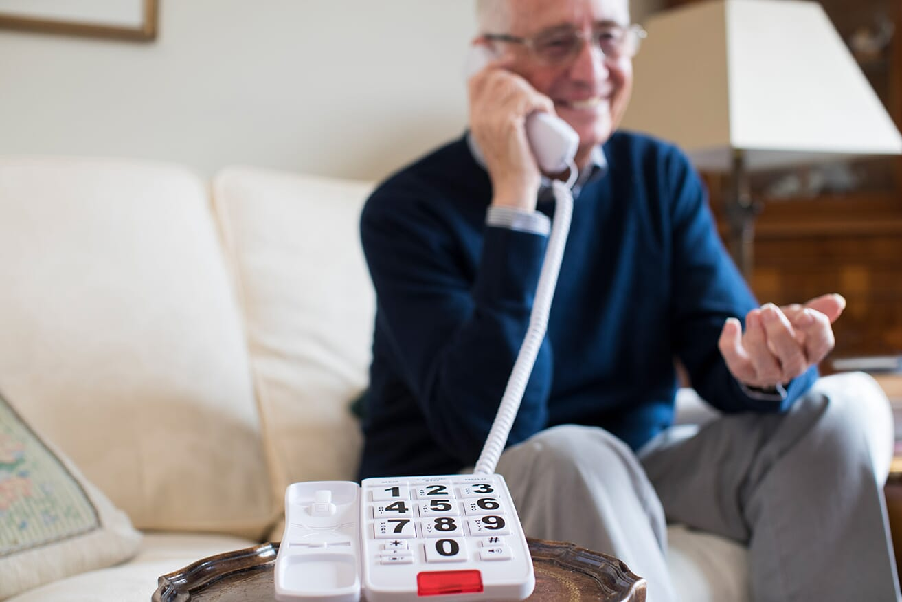 older man using big button telephone