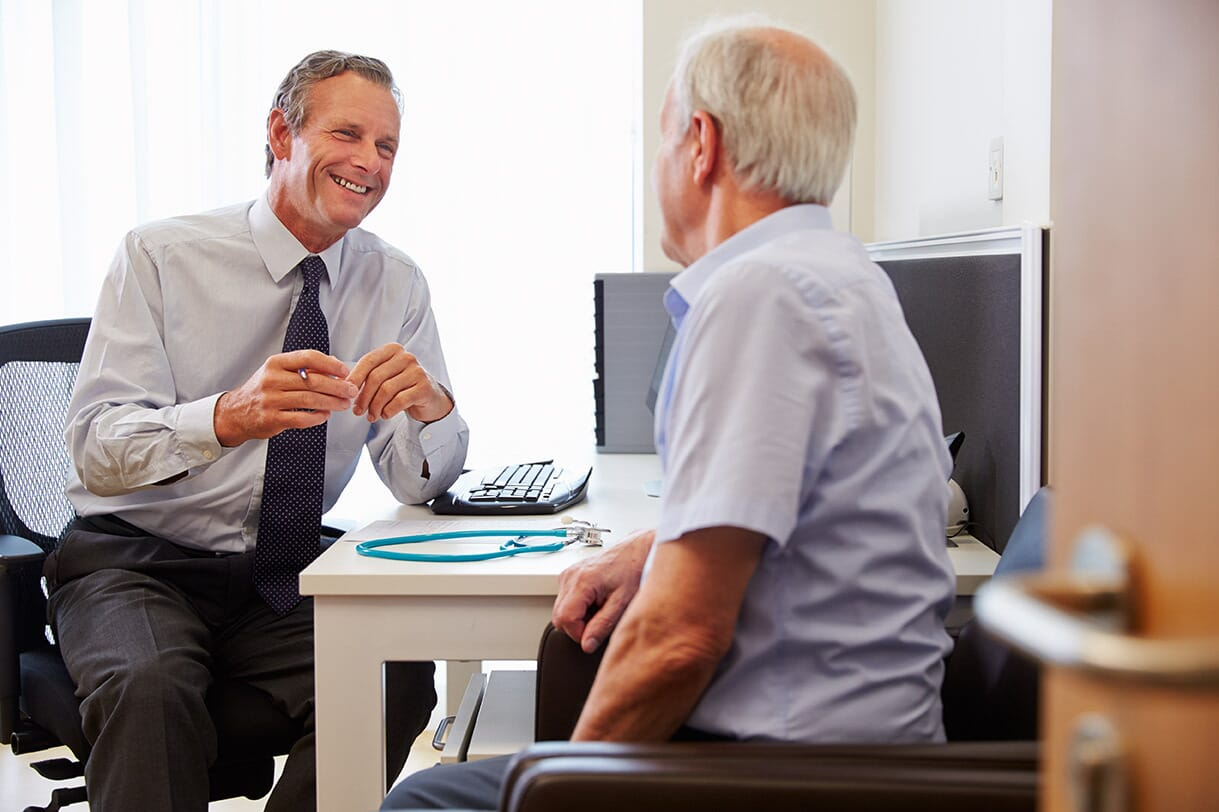 smiling man talking with his GP