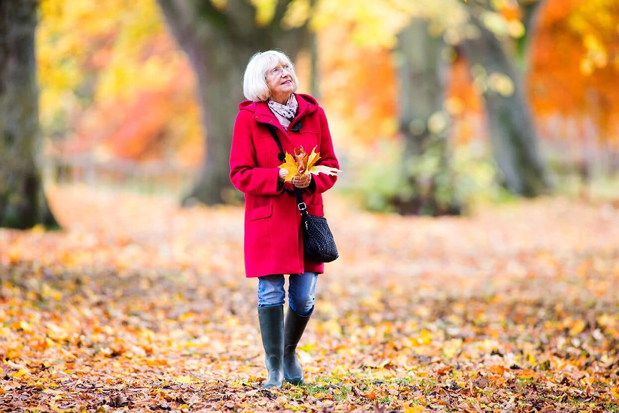 woman enjoying an autumnal walk through the woods